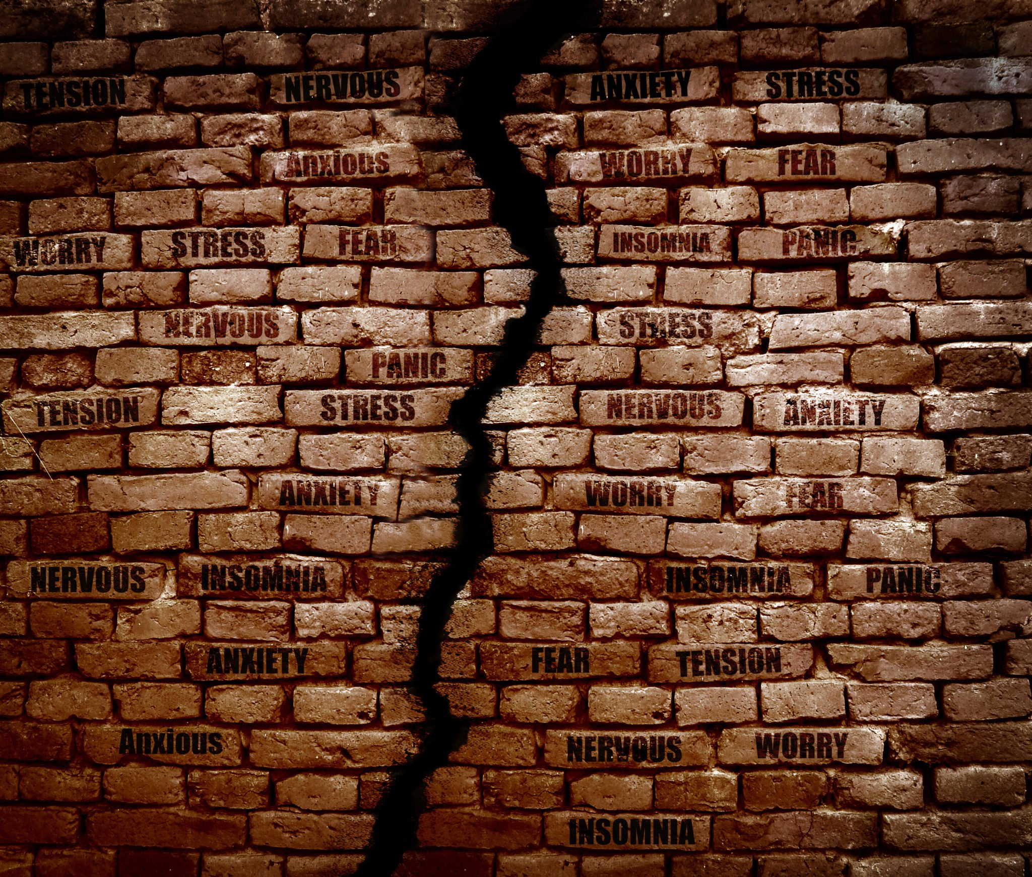 Crack in a brick wall with Stress, anxiety and various related messages