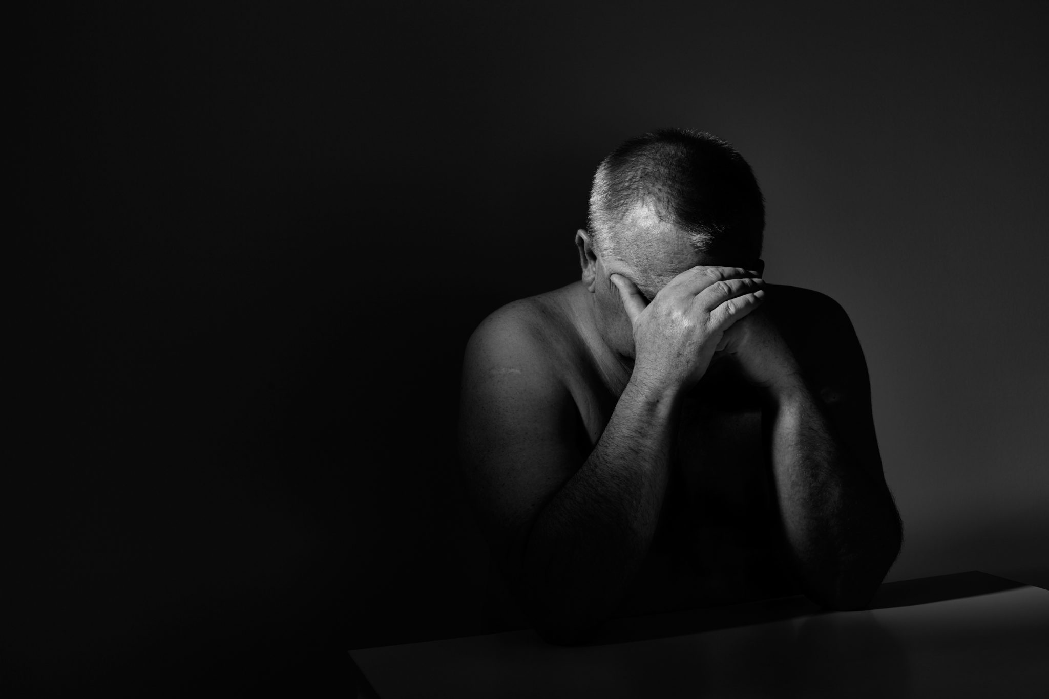 Dramatic black and white close up portrait of aged man sitting with hands on his face against wall - depression concept