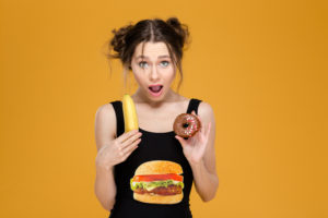 Wondered woman in designer top holding healthy and unhealthy food