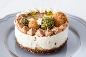 Raw vegan cake with lime, banana and chocolate, decorated with lime zest and chocolate balls on a grey plate on a light background