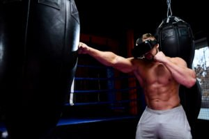 Muscular boxer with glasses of virtual reality hit black punching bag in dark gym