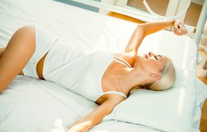smiling woman waking up at bedroom