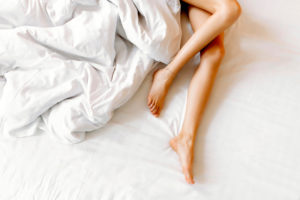 Slim, perfect and beautiful crossed woman legs on bed
