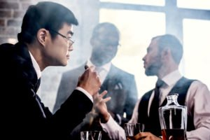 Multiethnic group of businessmen smoking and drinking whisky indoors
