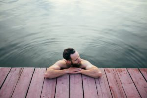 Man relaxing and swimming in the lake or a wimming pool